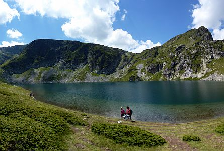 walkers walking around lake in the rila mountains in bulgaria