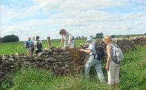 people climbing over a stile during a walking holiday