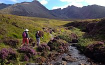 Pleople walking on a trail towards mountains in Scotland