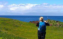 A female hiker walking on a green field towards the sea