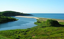 Beautiful landscape, river flows into the sea, wide sandy beach in between