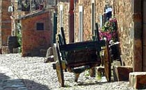 Old horse-cart in a cobbled street parked agaist a stone wall