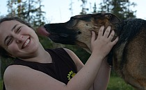 Smiling girl licked by a dog