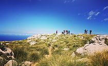 People standing on a cliff overlooking the sea