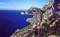 A man walking on a rocky trail along a cliff