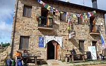 Walkers resting outside an inn along the route to Santiago. The building is decorated with multicoloured flags.