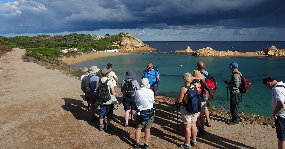 Group of walkers gathered around a man, beautiful turquoise sea and dark sky in the background