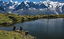 Hikers walking by a mountain lake, snow peaks in the background