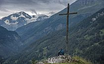 Man maditating on a giant cross overlooking a valley