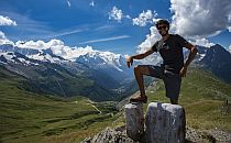 Man posing for a photo, a stunning view of mountains and valley behind
