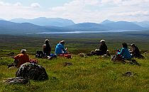 Group of people having picnic lunch, a lake and mointains in the background