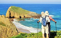 A pair of hikers looking at a scenic coastal landscape in Portugal's Algarve