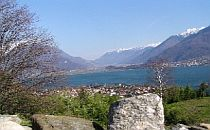 View over Lake Como with an Italian town in the the foreground on the lake's shore and high snowcapped mountains in the background.