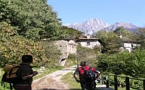 People walking over a bridge towards a small Italian village with high mountains in the background.