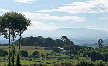View across fields and hills towards high mountains in the distance