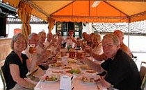 Group of people eating lunch together on a table outdoors under an orange canopy