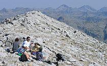 Walkers having a break on a rocky hill