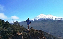 Hiker posing in fornt of a snowy peak