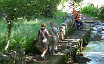 A small group of walkers going along a stream.