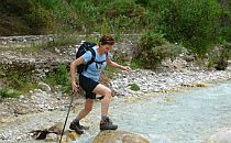 Woman with walking equipment crossing a small river by stepping on stones
