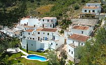 Small Andalucian village with white houses against a green mountainside. A swimming pool in front of one of the houses.