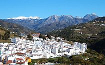 The village of Torrox with many white houses. Situated on a mountain side with snowcapped mountains in the background.