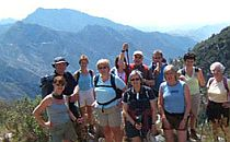 Group of walkers with guide posing in front of a mountainous landscape in Spain