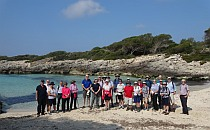 Big group of people posing for a picture on a sandy beach