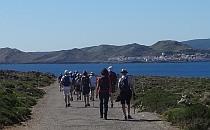 People walking on a wide road; sea, mountain hills and a city in the distance