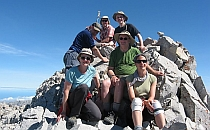 Group of walkers posing for a photo on a rocky hilltop