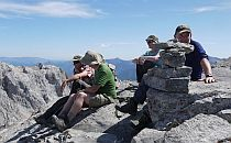 Group of walkers taking a break, sitting on a rocky formations