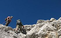 Two people climbing a rock formation in Picos de Europa