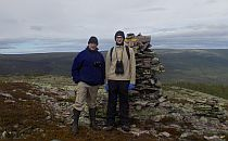 Two hikers posing in front of a high stone pile