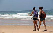 two young women hiking along a sandy beach