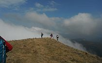 Group of people walking on the endge of a high plain, a low cloud covering the space below