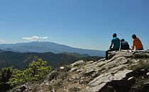 People sitting on a cliff overlooking many low hills