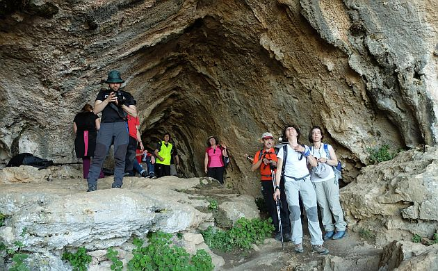 Group of hikers on the front of a cave