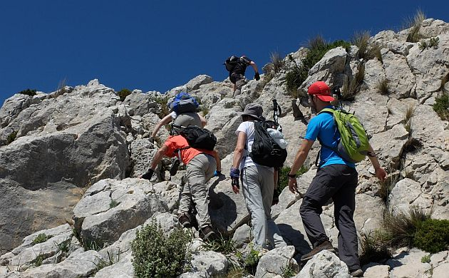 Group of hikers climbing steep montain path