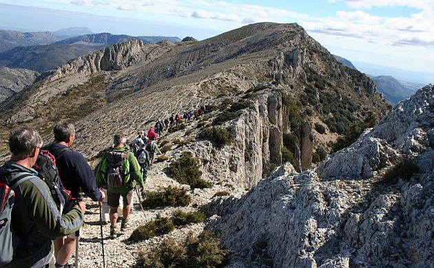 Group of walkers hiking a mountain top trail