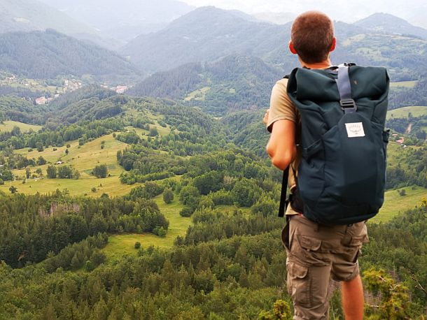 Man with Osprey backpack looking out over mountain valley