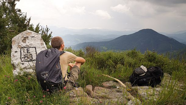 man with backpack sitting on a mountain-top