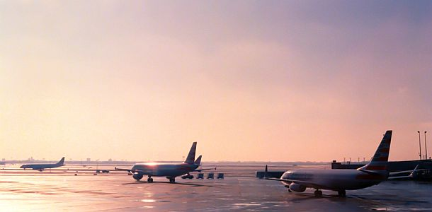 airplanes taxiing at an airport runway