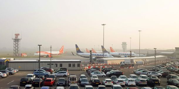 cars at airport parking with planes in background