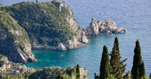 Big rocky hills ending in the sea, green trees as a frame, isle of Corfu, Greece