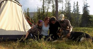 Group of hikers and a dog hugging on a green meadow next to a big tent during their guided walking holiday in Scotland