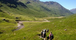 People walking on a trail in a valley during their guided walking holiday in Scotland