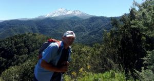 The guide for this walking holiday posing for a photo, snowy peak and green forests in the background