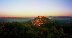 hilltop village surrounded by forest at dawn