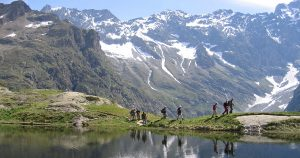 Group of hikers walking by a mountain lake, snowy peaks in the background